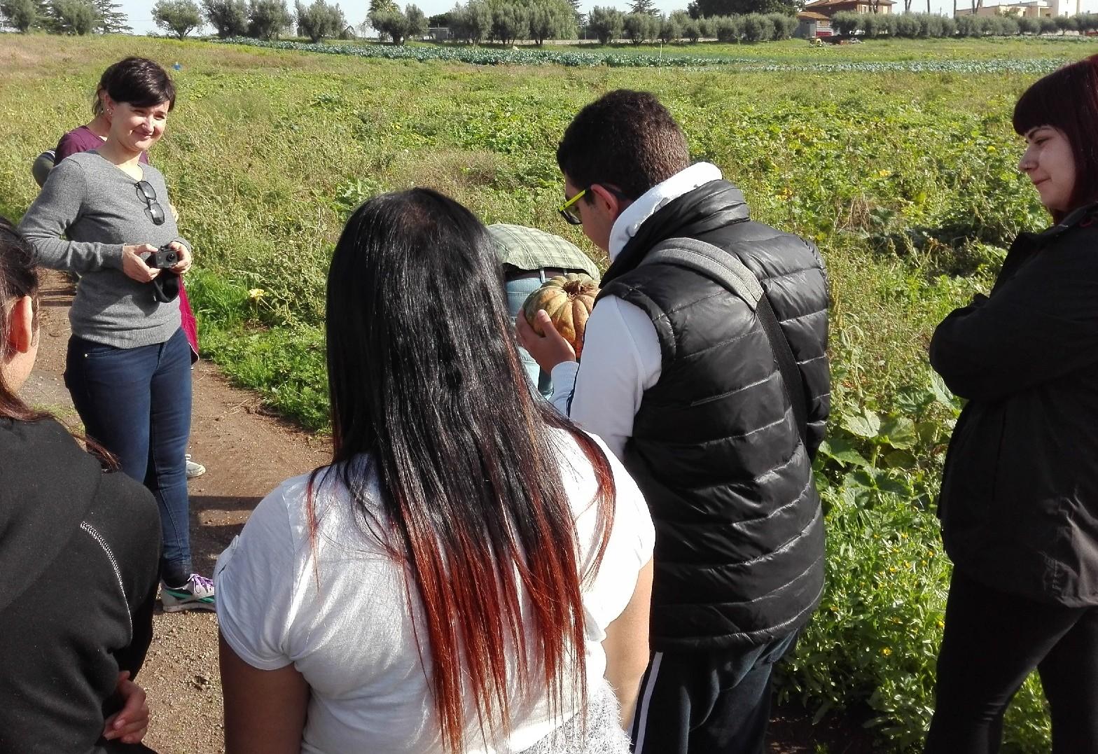 Durante la prima delle Giornate di Agricoltura Sociale, un educatore di Kairos, Andrea, passa la zucca ad un ragazzo al suo primo giorno in azienda